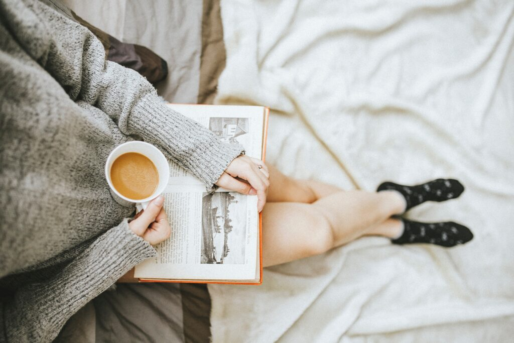 a woman reading on her bed with a cup of coffee