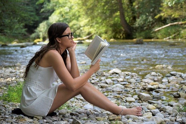 a woman reading on the river bank