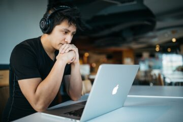 a man looking at his computer with headphones